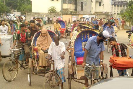 mode transport: Dhaka, Bangladesh - September 17th, 2007: Unidentified people on traditional rickshaws, cheap usual mode of transport