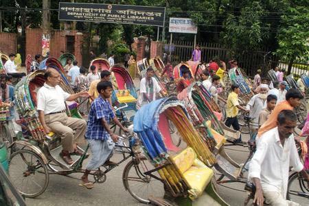 mode transport: Dhaka, Bangladesh - September 17th 2007: Unidentified people on traditional rickshaws, cheap usual mode of transport