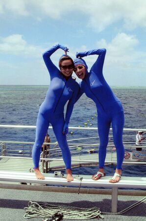 protective clothing: Australia, Queensland - March 2nd 2005: Two unidentified young Japanese women in protective clothing on barrier reef