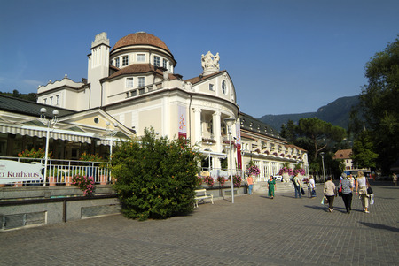meran: Meran, Italy - September 11th 2008: Unidentified people on promenade in front of spa building in the city in South Tyrol