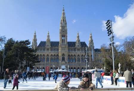 winterday: Vienna, Austria - February 21st 2010: crowd of unidentified people on a sunny winterday having fun on skating ring in front of the Vienna Townhall