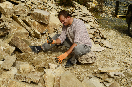 building material: Satovcha, Bulgaria - October 2nd 2013: Unidentified man working with hammer for stone plates, a traditional building material for home and garden