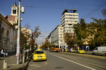 louise: Sofia, Bulgaria - September 28th 2013: Unidentified people, public tram and cars on Knyaginya Maria Louise Boulevard, left the Central Sofia Market building