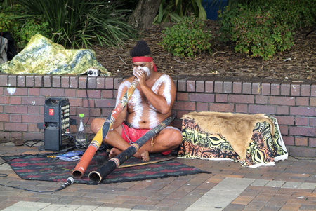 aborigine: Sydney, Australia - February 8th 2008: Aborigine with traditional didgeridoo and modern equipment playing on Circular Quay
