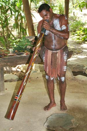 traditonal: Kuranda, Australia - March 1st 2005: Unidentified Aborigine with traditonal instrument named didgeridoo playing