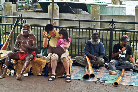 Sydney, Australia - February 8th 2008: Unidentified Aboriginal didgeridoo with traditional and Asian tourists on Circular Quay