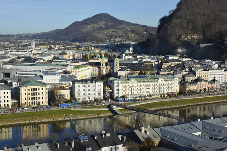 salzach: Salzburg, Austria - December 26th 2015: Cityscape with reflections and unidentified people walking along river Salzach and Markart bridge