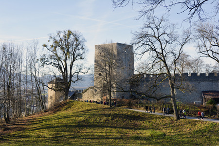 fortification: Salzburg, Austria - December 26th 2015: Unidentified people enjoy a walk on sunny winter day along the wall of fortification on Moenchsberg hill