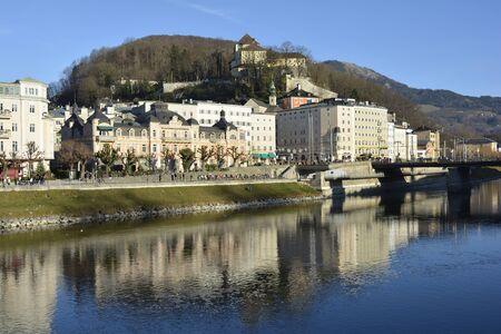 salzach: Salzburg, Austria - December 26th 2015: Unidentified people on promenade along Salzach river with buildings and Capuchin monastery
