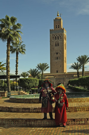 tourist attraction: Marrakesh, Morocco - November 23rd 2014: Unidentified water carrier in traditional costume in front of Koutoubia mosque, landmark and tourist attraction