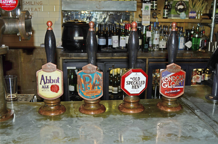 dispensing: London, Great Britain - January 16th 2016: Dispensing equipment for different beers in a traditional pub