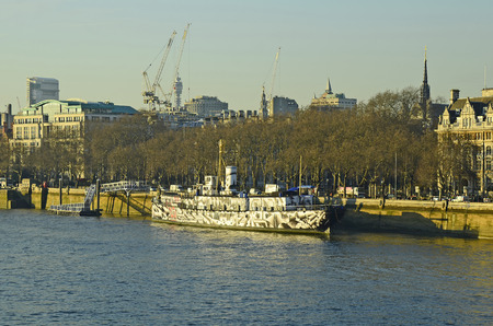 artful: London, Great Britain - January 19th 2016: Artful painted ship on river Thames and different buildings and cranes behind