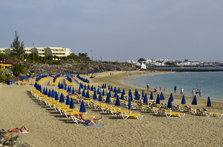dorada: Playa Blanca, Canary Island, Spain - January 15th 2012: Unidentified tourists enjoy a sunny day on the beach of Playa Dorada in Lanzarote Editorial