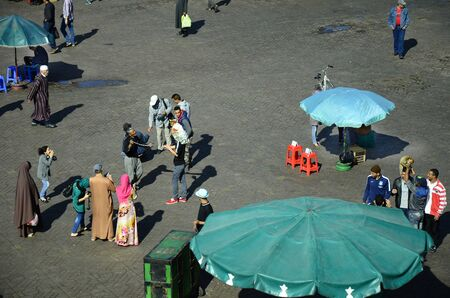 preferred: Marrakesh, Morocco - November 23rd 2014: Unidentified people on Djemaa el-Fna, Unescoa world heritage site and preferred place for tourists and inhabitants, men with monkeys