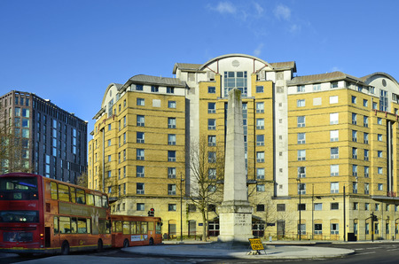 busses: London, Great Britain - January 15th 2016: Buildings and obelisk with traditional red double-decker busses on a roundabout in Southwark Editorial