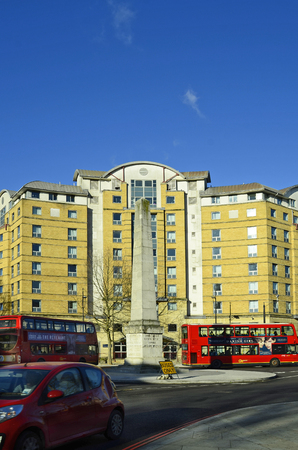 doubledecker: London, Great Britain - January 15th 2016: Buildings and obelisk with traditional red double-decker busses on a roundabout in Southwark Editorial
