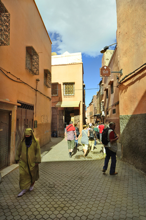 caftan: Marrakesh, Morocco - November 22nd 2014: Unidentified tourists by sighseeing in narrow street in the old precinct and woman in traditional kaftan with veil
