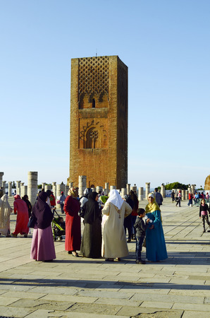 caftan: Rabat, Morocco - November 18th 2014: Unidentified tourists and woman in traditional Kaftan sightseeing on the place of Hassan tower - a landmark of the city Editorial