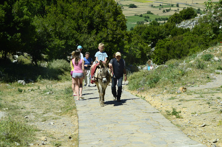 pack animal: Psychro, Greece - May 23rd 2014: Unidentified people and boy riding a donkey, on the way to  mystical cave of Zeus birth place aka Diktaean cave on Lassithi plateau in Crete