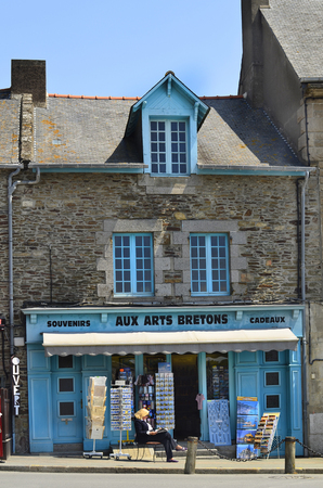 Cancale, France - June 10th 2011: Unidentified woman in front of a souvenir shop with colorful facade in the village in Brittany 新聞圖片