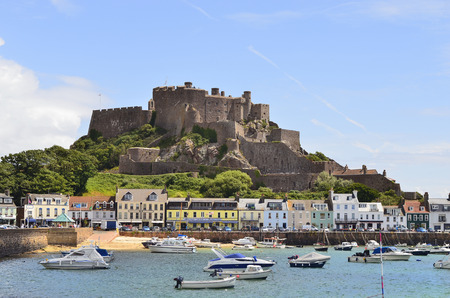 dependency: Gorey, United Kingdom - June 9th 2011: Village with harbor and Gorey castle aka Mont Orgueil castle, landmark and tourist attraction on Jersey, one of the channel islands
