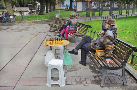 player bench: Sofia, Bulgaria - September 28th 2013: Unidentified chess player on park bench in public city park waiting for playing partner Editorial