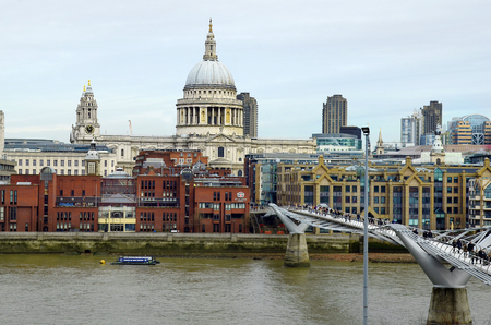millennium bridge: London, United Kingdom - January 17th 2016: Unidentified people on Millennium bridge over river Thames and St. Pauls cathedral with diefferent buildings
