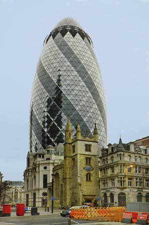 London, United Kingdom - January 17th 2016: The Gherkin building aka 30 St.Mary Axe and old church on Tower Hill district