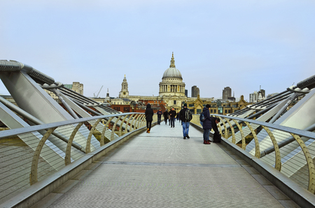 millennium bridge: London, United Kingdom - January 17th 2016: Unidentified people on Millennium bridge with St. Pauls cathedral behind