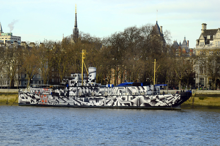 hms: London, United Kingdom - January 16th 2016: HMS President 1918 former HMS Saxifraga - in new outlook on Victoria Embankma nt on river Thames with spire of Royal Courts of Justice in background