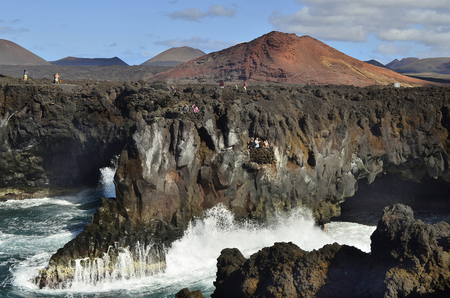 tourist attraction: Lanzarote, Spain - January 16th 2012: Unidentified tourists in lookouts watching the mighty surge of waves on the natural spectacle and tourist attraction Los Hervideros