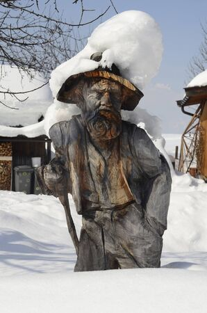 Austria, wood carving sculpture with snow Stock Photo