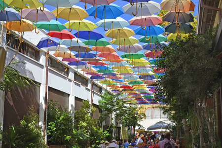 Nicosia, Cyprus - October 20th 2015: Unidentified people in restaurant with colorful umbrellas for sun protection