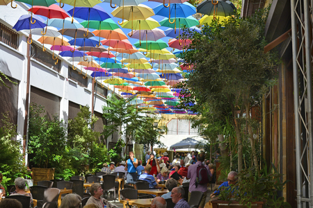 sun protection: Nicosia, Cyprus - October 20th 2015: Unidentified people in restaurant with colorful umbrellas for sun protection Editorial