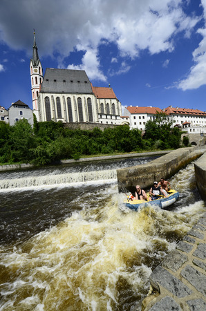 unesco in czech republic: Cesky Krumlov, Czechia - August 11th 2013: Unidentified people in rubber raft on Moldau (Vlatava) river with church of Saint Vitus in the Unesco World Heritage site in Bohemia, rafting on river Vlatava (Moldau) is a preferred watersport in this area