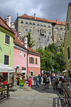 unesco in czech republic: Cesky Krumlov, Czech Republic - August 11th 2013: Unidentified tourists on small street with shops and colorful homes, part of the castle above in the Unesco World Heritage site in Bohemia Editorial