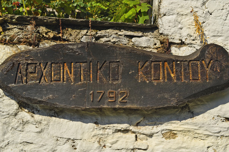 thessaly: Milies, Greece - September 25th 2011: Wooden board with greek characters and hotel name