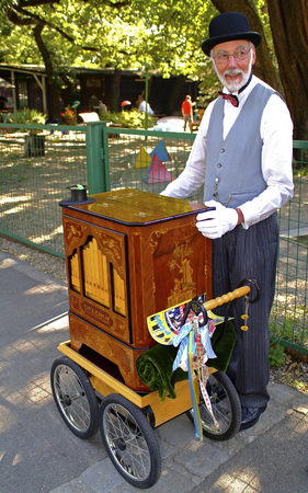 prater: Vienna, Austria - September 2nd 2005: Unidentified man playing barrel organ in Bohemian Prater Editorial