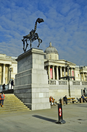 plinth: London, United Kingdom - January 19th 2016: Unidentified people and sculpture on fourth plinth, riderless horse skeleton from artist Hans Haacke on Trafalgar Square