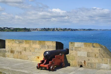 st  malo: France, Brittany, old cannon on the town wall of St. Malo with view to Dinard village