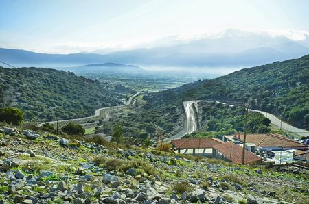 ida: Greece, Crete, Ambelos pass with mountain road to Lassithi plateau and snowy Ida range behind Stock Photo