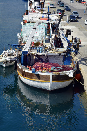 18th: Kavala, Greece - September 18th 2015: Fishing ship and cars at ferry terminal in the harbor of the city in Eastmacedonia Editorial