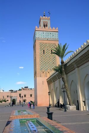 marrakesh: Marrakesh, Morocco - November 22nd 2014: Unidentified people and mosque with minaret in traditional style