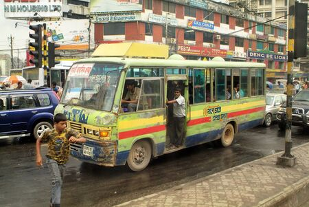 mode transport: Dhaka, Bangladesh - Setember 17th 2007: Unidentified people and battered public bus, usual mode of transport in the capital