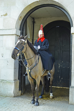 tourist attraction: London, United Kngdom - January 19th 2016: Unidentified honor guard on horse at  Horse Guard Parade building, traditional tourist attraction Editorial