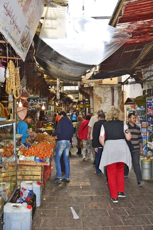 fes: Fes, Morocco - November 20th 2014: Unidentified people working in narrow street souk Fes el-Bali with different shops and goods
