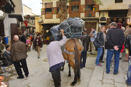 fes: Fes, Morocco - November 20th 2014: Unidentified man with horse laden with different goodson place es-Seffarine in souk Fes el-Bali