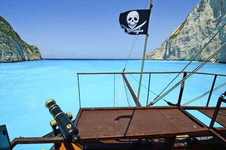 blackjack: Greece, Zakynthos Island, ship with blackjack flag and cannon on blue sea Stock Photo