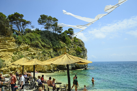 cameo: Zakynthos, Greece - May 24th 2016: Unidentified people on beach of tiny Cameo island with bar-restaurant in Ionean sea Editorial
