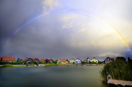 settlement: Austria, rainbow and thunder clouds over settlement with lake Stock Photo